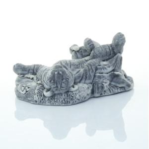Тигрица лежит на спине у пня
